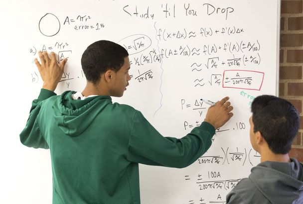 Devin Pegues, left, and Casiano Atienza work on a math problem during a recent class at the UW. This math workshop uses whiteboards and group problem-solving to bring engineering-level math to first-year students. Photo by Mike Siegel / The Seattle Times.