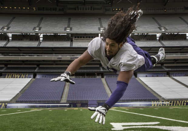 UW defensive end Hau'oli Kikaha flies through the air after practice at Husky Stadium in Seattle Wednesday morning. (Ellen M. Banner/The Seattle Times)