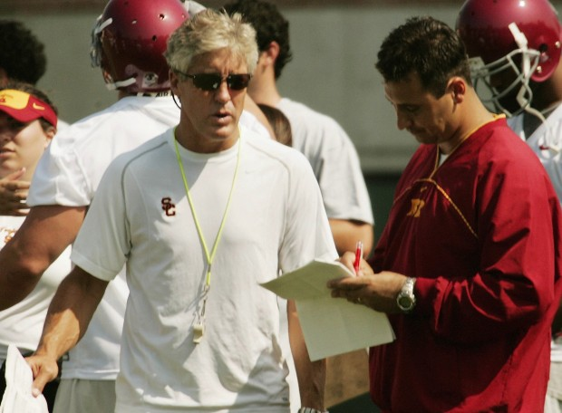 Then-USC head coach Pete Carroll, left, and assistant head coach Steve Sarkisian talk during the first day of Trojans' training camp on Aug. 4, 2005 in Los Angeles. (AP Photo/File)