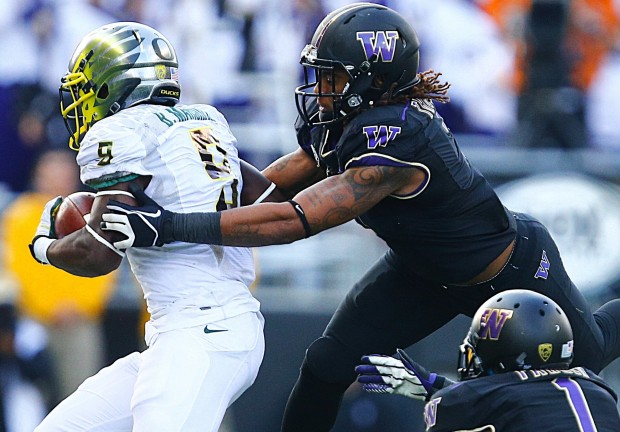 Oregon Ducks running back Byron Marshall, left, slips by the Washington defenders Shaq Thompson, center, and Sean Parker for a 23-yard rush in the second half at Husky Stadium on Saturday. (John Lok/The Seattle Times)