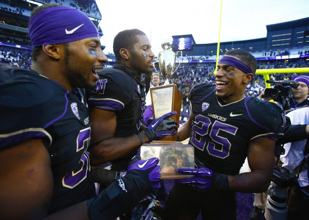 Bishop Sankey, right, celebrates winning the 106th Apple Cup with teammates Tre Watson, far left, and Kevin Smith after defeating the Washington State Cougars 27-17 at Husky Stadium on Friday, November 29, 2013, in Seattle, Wash. (John Lok/The Seattle Times)