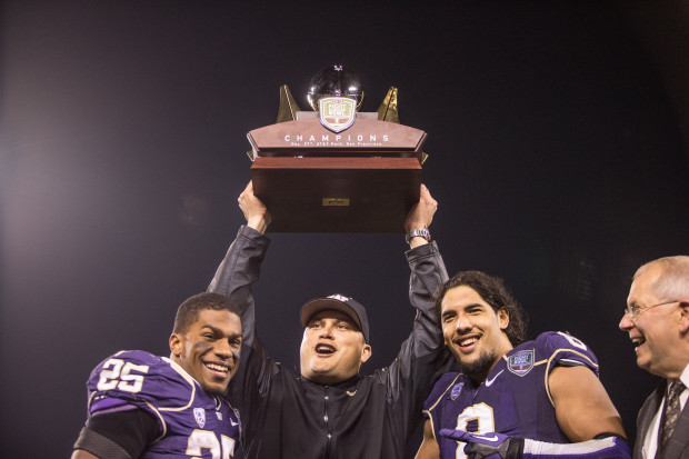 Marques Tuiasosopo holds the Fight Hunger Bowl trophy aloft with offensive and defensive players of the game, Bishop Sankey and Hau'oli Kikaha. (Dean Rutz/The Seattle Times)