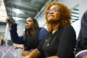 Shaundra Price, left, the mother of former UW quarterback Keith Price, and Gail Manuel, right, his grandmother, look on as Price performs drills at UW's Pro Day. (John Lok/The Seattle Times)