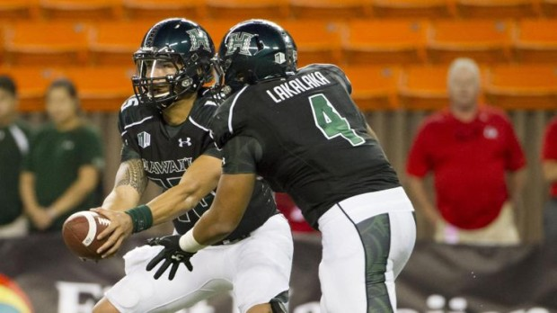 Hawaii quarterback Ikaika Woolsey (15) hands off to running back Steven Lakalaka (4) in a game last year in Honolulu. (Eugene Tanner/The Associated Press)