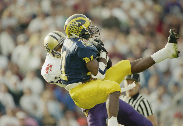 Washington's Walter Bailey, behind, intercepts a first quarter pass intended for Michigan's Desmond Howard (21), this year's Heisman trophy winner, at the Rose Bowl in Pasadena, Calif., on Jan. 1, 1992. (AP Photo/Bob Galbraith)