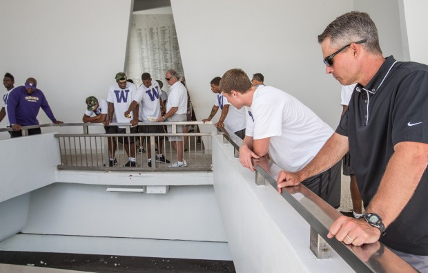 Washington coach Chris Petersen, right, stands aside and lets his players each drop flower petals into the water above the remains of the USS Arizona Friday in Pearl Harbor.  Petersen brought his team to the WWII memorial after their final practice before the season opener Saturday against Hawaii.