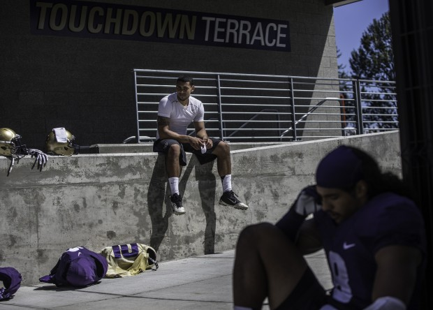 Quarterback Cyler Miles sits on a wall off the field at Husky Stadium before to talking to reporters Wednesday. (Dean Rutz/The Seattle Times)