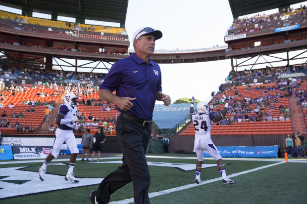 UW coach Chris Petersen runs onto the field before the start of the Huskies' game at Hawaii on Saturday. (Dean Rutz/The Seattle Times)