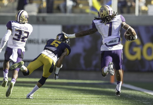 Shaq Thompson dodges his last Cal Bear, Darius White, and runs for 100 yards for a touchdown, scoring on a fumble recovery on the goal line. (Dean Rutz/The Seattle Times)