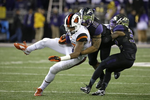 Oregon State's Jordan Villamin, left, is brought down by Washington's John Timu and Budda Baker in the second half of an NCAA college football game Saturday, Nov. 22, 2014, in Seattle. Washington won 37-13. (AP Photo/Elaine Thompson)