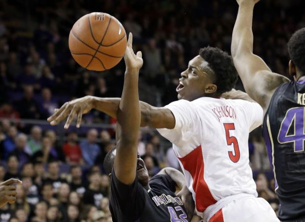 Arizona's Stanley Johnson (5) drives between Washington's Andrew Andrews, left, and Nigel Williams-Goss during the first half of an NCAA college basketball game Friday, Feb. 13, 2015, in Seattle. (AP Photo/Elaine Thompson)