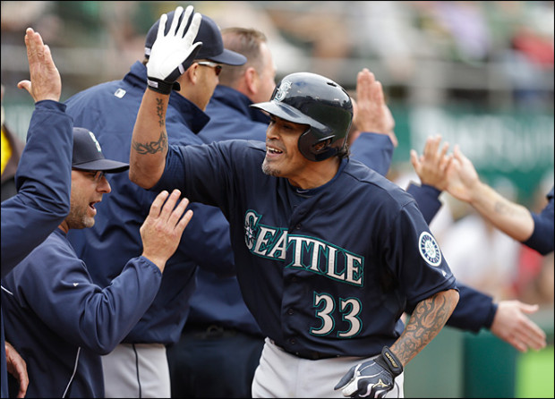 Henry Blanco is mobbed by teammates after his grand slam at age 41 years, 290 days, gave the Mariners all their runs in a 4-0 win over the Oakland Athletics back in June. Photo Credit: AP