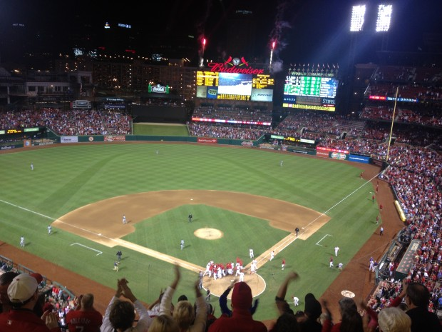 The St. Louis Cardinals celebrate at home plate as a passed ball by Mike Zunino allows winning run to score in Seattle's 2-1 loss in 10 innings.