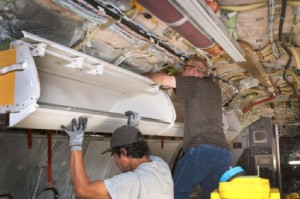 Workers install larger bins for carry-on luggage on an American Airlines  Boeing 737, in Tulsa, Okla. But carry-on space is still jammed on planes. (American Airlines / AP, 2012)