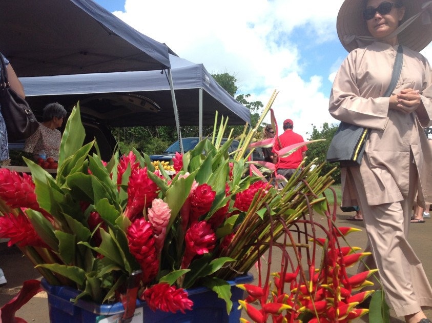 A shopper passes a flower stand at the Saturday farmers market at Kauai Community College. (photo by Brian J. Cantwell / The Seattle Times)