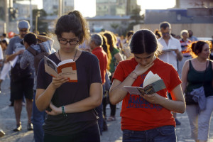 People stand and read books during a silent protest at Taksim Square on June 20, 2013 in Istanbul, Turkey. The protests began in May, with environmentalists upset over plans to build in Gezi Park, and has grown into a broader demonstration against Prime Minister Tayyip Erdogan's government.  [Baris Acarli/Getty Images]