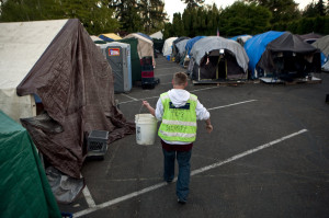Heather Kuykendall, 29, does some cleaning during her security shift at Tent City 3 in Shoreline. The security shifts are among requirements that campers must fulfill. Some campers say activism also is a stringent requirement. (Bettina Hansen / The Seattle Times)