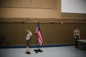 Eric Hoelscher, 10, salutes the American Flag during a color guard flag ceremony to mark the end of the Troop 574 Boy Scouts of America's meeting inside the gymnasium at Cedar Park Church in Bothell, on Monday, June 17, 2013. [Marcus Yam, The Seattle Times.]