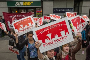 May 30: Strikers marching to improve wages among fast-food jobs, outside a Subway restaurant in Fisher Plaza, where they convinced the one employee on shift to walk off the job and shut the restaurant down. [Dean Rutz, The Seattle Times.]