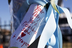 "A handwritten note saying ""Your Navy Yard Neighbors Send (Love) and Prayers"" is taped to a post across the street from an entrance to the Washington Navy Yard, two days after a gunman killed twelve people and was killed himself inside the Navy Yard in Washington, on Sept. 18, 2013. [AP Photo/Jacquelyn Martin]"
