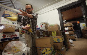 Joe Gruber, executive director of the University District Food Bank, throws out a slightly old banana as he goes through fruit that will be given out at the food bank. The University District Food Bank is one of more than 25 food banks serving Seattle. [Ellen M. Banner, The Seattle Times.]