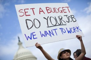 A woman holds a sign during an event with the Democratic Progressive Caucus with furloughed federal employees blaming House Republicans on the government shutdown on Capitol Hill on Friday, Oct. 4, 2013 in Washington. (AP Photo/ Evan Vucci)