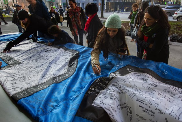 "Smeeta Hirani from Seattle signs the 12th man flag in front of the Seattle Public Library downtown as her mom Muntaz Hirani from Dallas, Texas watches. The ""Tattered 12 "" Flag that flew over the Space Needle during that game has become a symbol of the heart and grit of the Seahawks. ( Ellen M. Banner / The Seattle Times)"