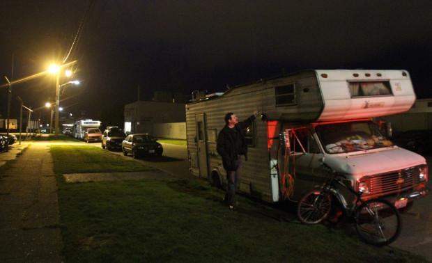 Seattle University research fellow Graham Pruss, who has studied homeless vehicle camping, checks on an  RV in Ballard ALAN BERNER / SEATTLE TIMES