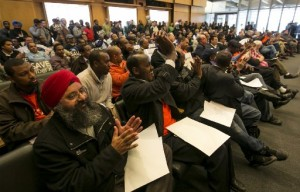 From left, Parmjit Singh, an owner-driver of a FarWest taxicab, and Said Fatah, a flat-rate driver, cheer as the Seattle City Council approves a cap and stronger regulations on Transportation Network Companies (TNCs) like uberx, Lyft and Sidecar in a standing-room only meeting packed with supporters from both the TNCs and taxi/for-hire drivers at Seattle City Hall Monday March 17, 2014. (Photo by Bettina Hansen/The Seattle Times)