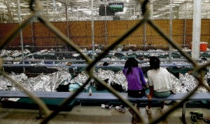 In this Wednesday, June 18, 2014, file photo, two young girls watch a World Cup soccer match on a television from their holding area where hundreds of mostly Central American immigrant children are being processed and held at the U.S. Customs and Border Protection Nogales Placement Center in Nogales, Ariz. As of Thursday, July 17, 2014, immigrant children caught crossing the Mexican border into Texas illegally and alone are no longer being sent to a massive Nogales facility. (AP Photo/Ross D. Franklin, Pool, File)