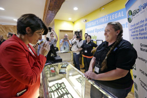 Alison Holcomb, left, checking out the products on the first day legal marijuana sales. (Elaine Thompson / AP)