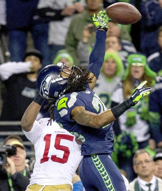 Richard Sherman tips Colin Kaepernick's pass in the end zone, setting up the interception by Malcolm Smith to seal the win for  the Seahawks over the 49ers  in the NFC Championship Game. (Photo by Dean Rutz / The Seattle Times)