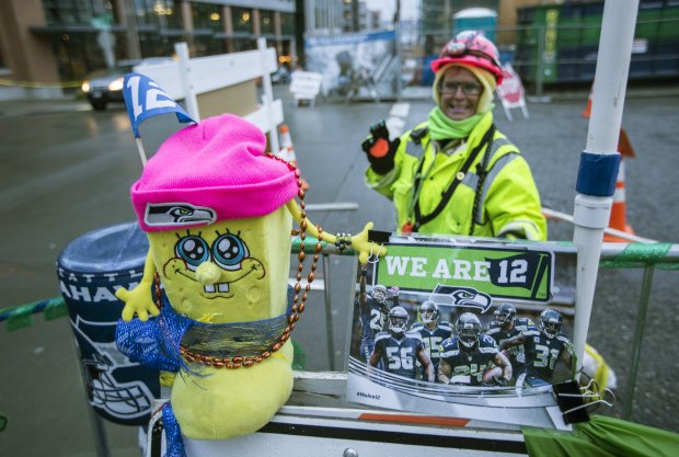 Construction worker Ruby Pippin (in backround) has decorated the corner of Thomas Street and Terry Avenue North with all things Seahawks. (Steve Ringman / The Seattle Times)