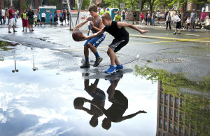 Cameron Teplicky, of Bellevue, left, and Nick Page of Deer Park try to control a loose ball before splashing into a puddle  on Riverside Avenue after rain soaked Hoopfest.    Photo by Dan Pelle, Spokesman-Review