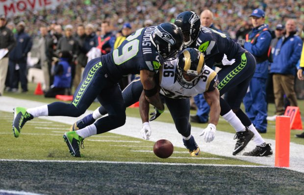 Seahawks safety Earl Thomas, left,forces a fumble from Rams running back Benny Cunningham,  which resulted  in a touchback in the fourth quarter of Seattle's victory last Sunday.  Mike Siegel / Seattle Times staff