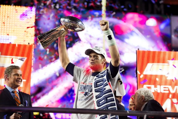 Tom Brady holds his fourth Lombardi Trophy aloft after rallying the Patriots past the Seahawks in Super Bowl XLIX. Dean Rutz / Seattle Times staff