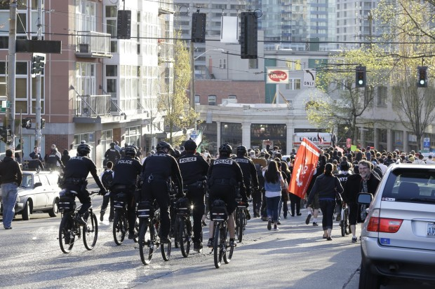 A sizable contingent of police follow demonstrators on bike. (Photo by Dean Rutz / the Seattle Times)
