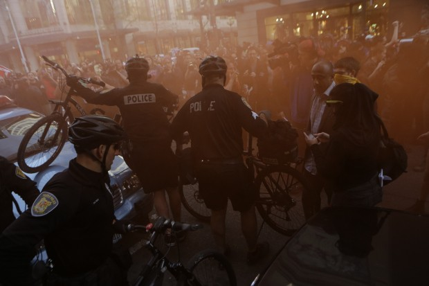 Police create a barrier with their bicycles as protesters deploy smoke and march downtown near Sixth Ave. and Pike St. downtown. (Photo by Bettina Hansen / The Seattle Times)
