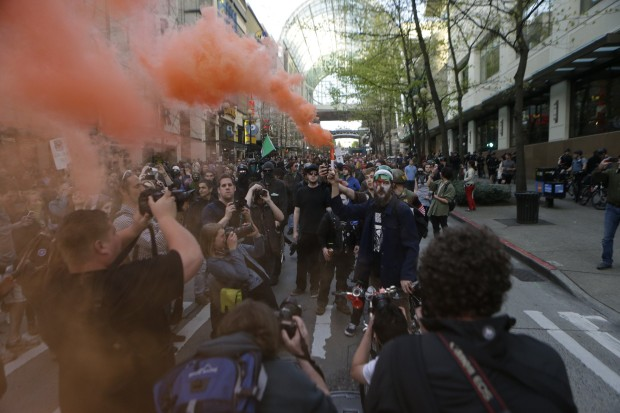 A protester discharges red smoke as the march pauses near the Convention Center on Pike Street. (Photo by Bettina Hansen / The Seattle Times)
