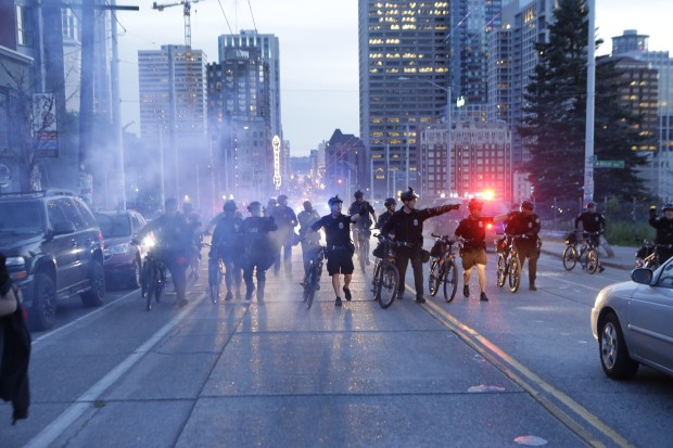 Police form a barrier near Pine and Boren, pushing protesters toward Seattle Central Community College. (Photo by Bettina Hansen / The Seattle Times)