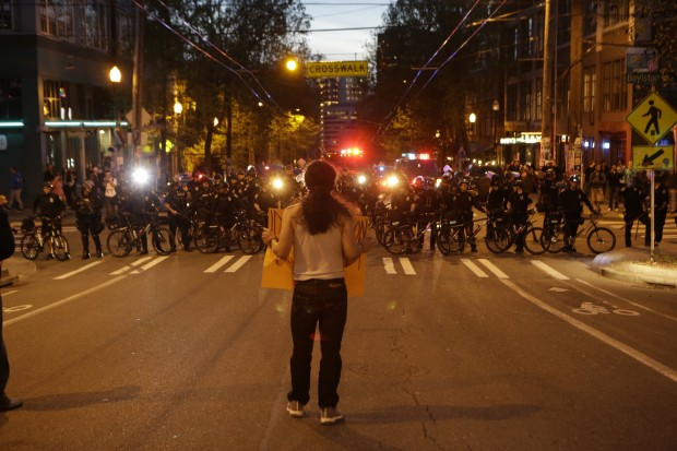 A protester stands in the middle of the street near a line of Seattle police. (Photo by Bettina Hansen / The Seattle Times)