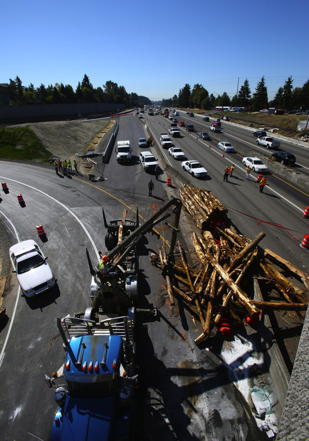 A logging truck dumped a full load of logs onto Interstate 405 and the northbound ramp at NE 160th St. Wednesday morning backing up traffic for miles in both directions. (Photo by Mark Harrison / The Seattle Times)