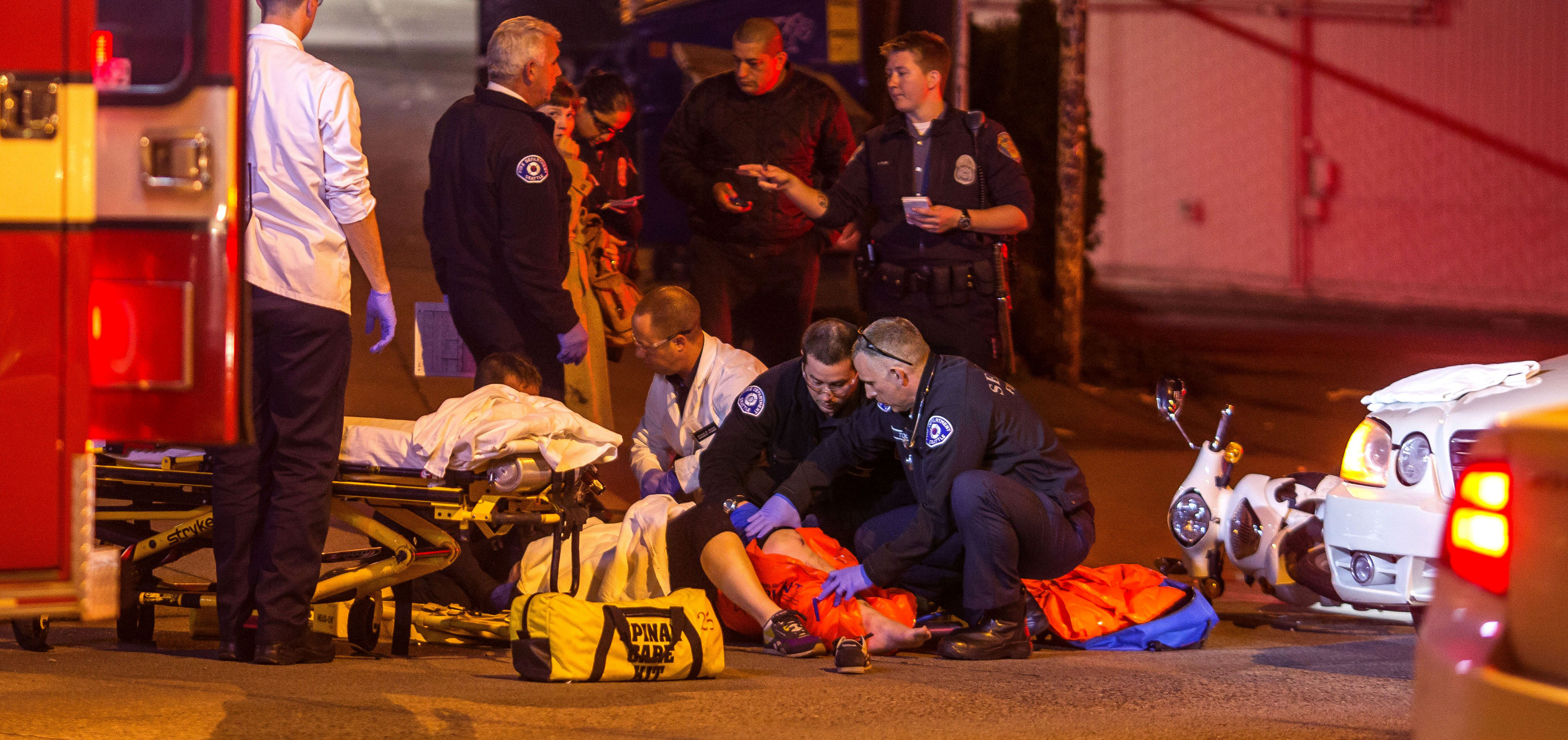 Paramedics tend to a woman who collided with a car while driving a scooter on East Olive Way Thursday night. The extent of her injuries were not immediately known. (Dean Rutz / The Seattle Times)