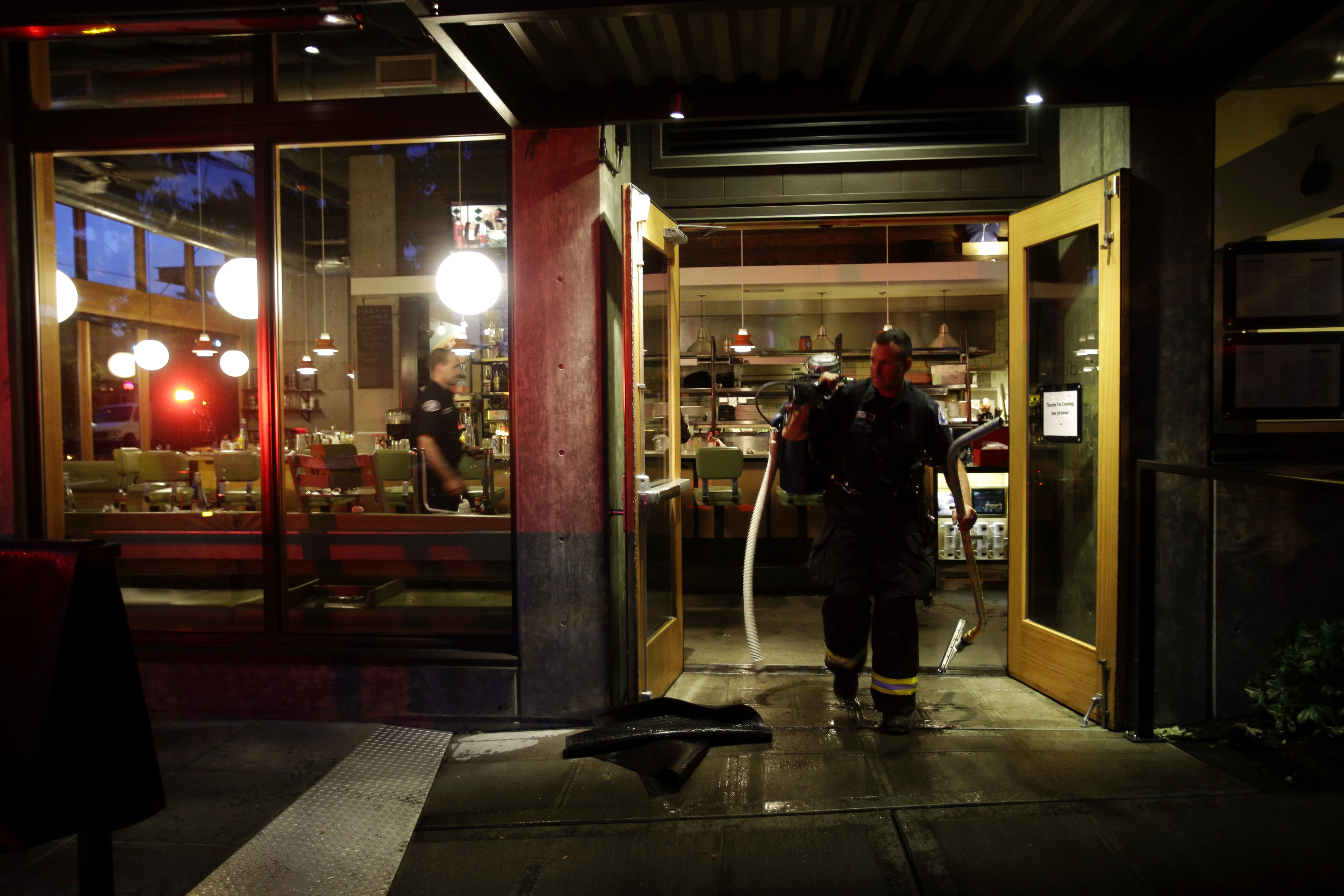 Seattle firefighters mop up a small fire at the Skillet Diner on Capitol Hill Thursday evening. The restaurant's crew said a gas line fire was quickly extinguished, and they hope to reopen Friday morning. (Dean Rutz / The Seattle Times)