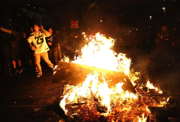 Fans celebrate around a bonfire in the University District. (Photo by Lindsey Wasson / The Seattle Times)