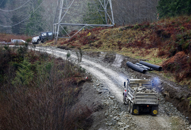 A truck hauls rocks up the road Washington State Department of Transportation crews are making to allow emergency vehicles and construction crews access to the Darrington side of the mudslide on Highway 530. (Lindsey Wasson / The Seattle Times)
