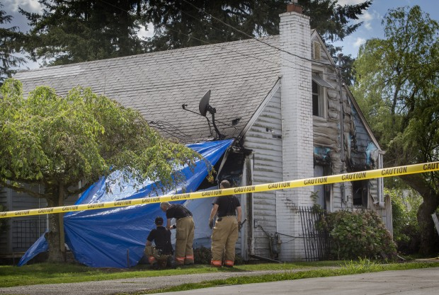 Firefighters secure a tarp at the front of a house located at 12221 78th Ave. S. in Skyway where a fire took the life of person Monday afternoon. (Photo by Ellen M. Banner / The Seattle Times)