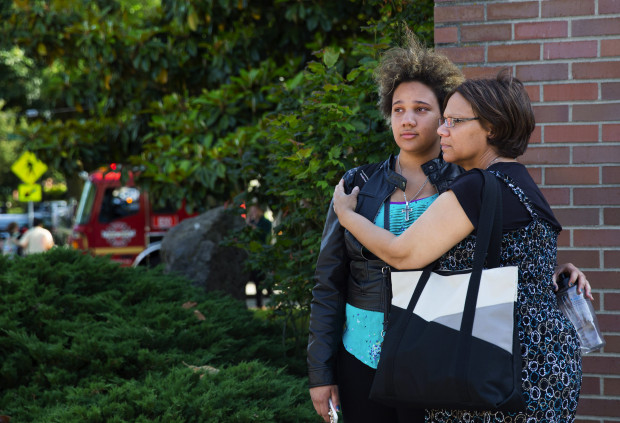 Gloris Jones, 20, and her mother, Mary Jones, compose themselves outside the scene of a shooting at Seattle Pacific University. Gloris, 20, said that she received a text message from a friend who had been shot. (Photo by Marcus Yam / The Seattle Times)