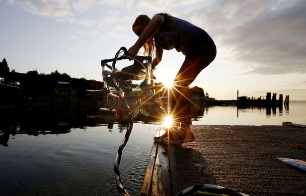 Annika Hustad lowers her team's robot into the waters of Saratoga Passage from the marina in Langley on Whidbey Island. This was its initial test. The team heads for an international competition in Romania this week. (Photo by Alan Berner / The Seattle Times)