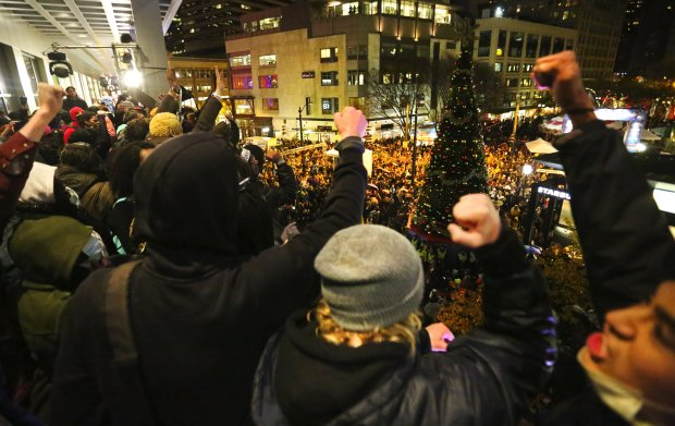 Scores of protesters joined sightseers and shoppers in downtown Seattle on Friday night. Many of the protesters were demonstrating against the grand jury decision to not indict an officer in a teen's death in Ferguson, Mo. Westlake Center closed three hours early after protesters moved into the mall. Above, protesters gather on the top floor of the mall overlooking the Christmas tree lighting ceremony. (Photo by Ken Lambert / The Seattle Times)